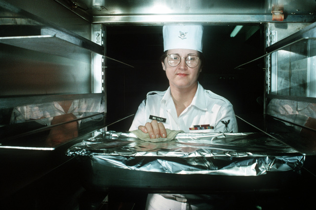 Mess SPECIALIST Third Class (MS3) Velma Finley removes a pan of noodles from a warming rack in the galley at Naval Air Station Key West