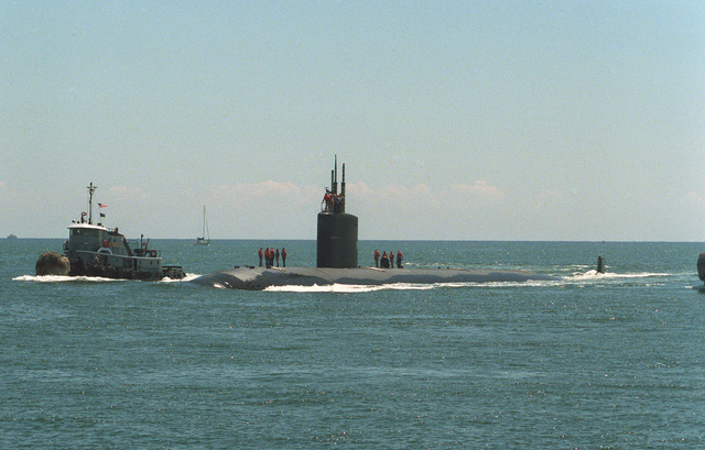A port quarter bow view of the USS ALEXANDRIA (SSN 757) being assisted by a tugboat, entering port at Port Everglades, Florida