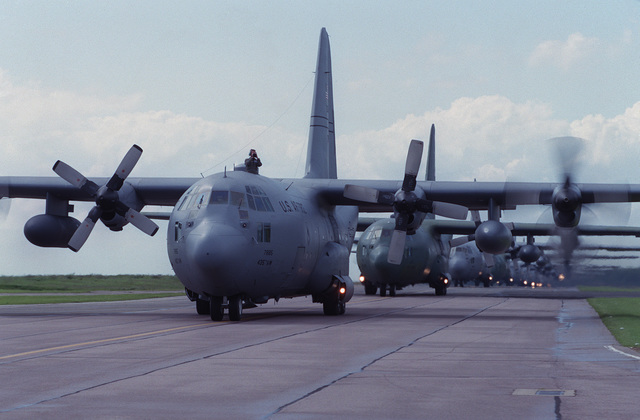 A line of C-130s taxi back in after a practice run for Operation Overlord '94. The three squadrons deployed were the 2nd Airlift Squadron (ALS) Pope AFB, North Carolina, 37th Airlift Squadron (ALS) Rhein-Main AB, Germany and the 41st Airlift Squadron (ALS), Pope AFB, North Carolina. The purpose of the deployment was to airlift the 82nd and the 101st Airborne troops into France to commemorate the 50th anniversary of the D-Day landings in Operation Overlord