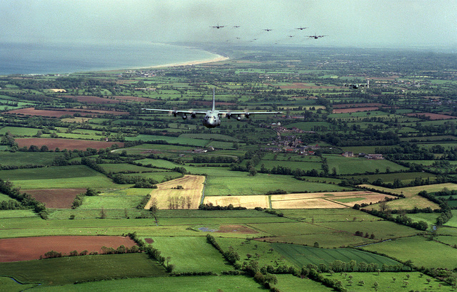 Three Squadrons are pictured in the background flying over the Normandy beach during a practice of Operation Overlord '94. The three squadrons are the 2nd Airlift Squadron (ALS) Pope AFB, North Carolina, 37th Airlift Squadron (ALS) Rhein-Main AB, Germany and the 41st Airlift Squadron (ALS), Pope AFB, North Carolina. They deployed to RAF Alconbury, England to airlift the 82nd and the 101st Airborne troops into France to commemorate the 50th anniversary of the D-Day landings