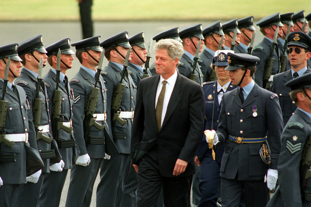 President William Jefferson Clinton walks through the ranks of the Number two and the Number 66 Royal Air Force Squadrons in review. Clinton is escorted by Squadron Leaders Tony Galloway and Andrew Steele. MAJ. Michelle Johanson serves as an Air Force Aid for the United States. President Clinton visits RAF Mildenhall before attending the Memorial ceremony held at Maddingley, the American cemetery in Cambridge, England