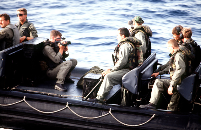PH2(NAC) Cinelli from Combat Camera, Norfolk, VA, videotapes SEALs and security personnel as they ride the rigid hull inflatable boat (RHIB) to inspect the Danish ship, VINELAND SAGA (not shown) as part of the US Embargo Policy.(Exact date unknown)