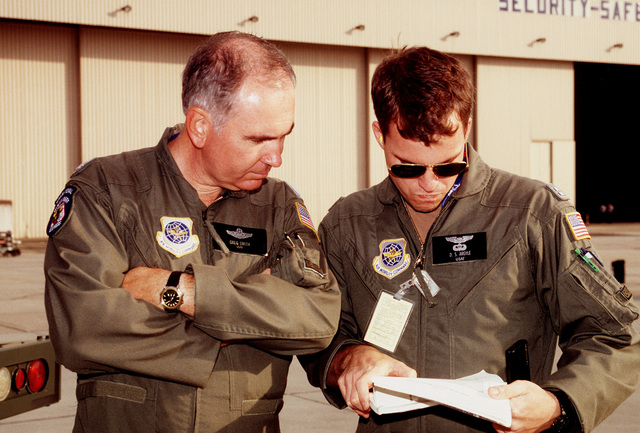 LT. COL. Greg Smith (left), mission commander for the airflow and Captain David S. Argyle, deputy mission commander, both from the 438th Airlift Wing, McGuire AFB, NJ, look over the fuel planning documents for the mission