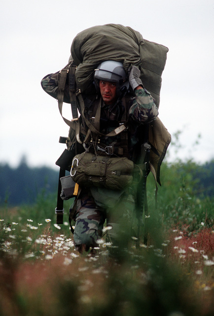 Seconds after jumping from a C-141 Starlifter to his landing zone, this member of a Combat Control Team carries his 40 pound pack. He will secure the airfield during the U.S. Air Force Air Mobility Command's annual mobility competition which began on June 26 at McChord AFB, Washington