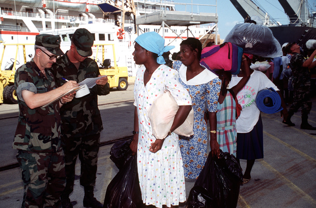 CW03 J.D. Barrett, a DMPITS (Deployed Mass Population Identification and Tracking System) worker, and an Army Military Policeman, check rosters received from the hospital ship USNS COMFORT (T-AH-20) as the migrants are moved from the COMFORT to the control of Joint Task Force (JTF) 160.(Exact date unknown)