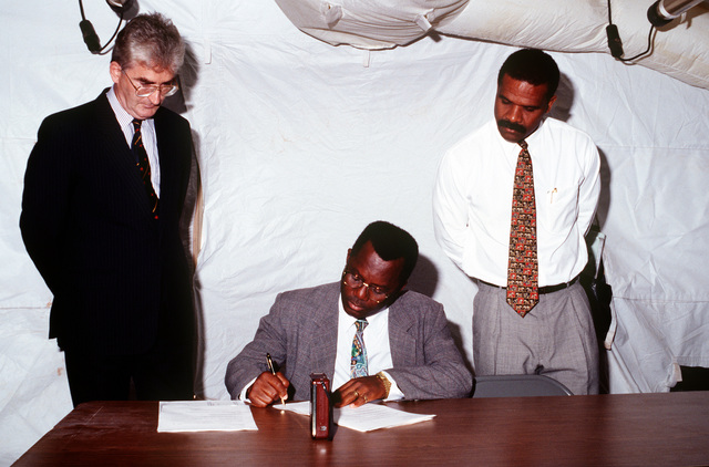Robert Hall, Minister of Immigration, Labor and Works, signs the Memorandum of Understanding between the United States and the Grand Turk and Caicos Islands as state department representative Richard Devine and CHIEF Minister and acting Governor Charles Washington Misick look on.(Exact date unknown)