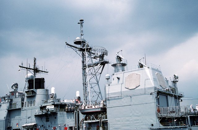 A port side view of the superstructure of the guided missile cruiser USS NORMANDY (CG-60). On the fore mast is the dome shaped SPQ-9A surface gun control radar with a SPG-62 radar illuminator to the left. On the main mast is the SPS-49(V)6 air-search radar with the small dome shaped SPS-64(V)9 navigational radar above and forward on the mast. Two SPG-62 radar illuminators are on top of the aft deck house with a QE-82 antenna for WSC-3 UHF SATCOMM off to the right. The two panels in the aft deck house are the SPY-1A radar fixed antenna array
