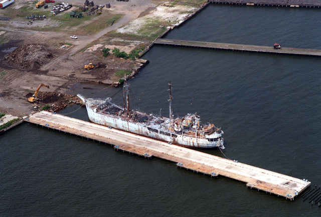 An aerial port quarter view of the former U.S. Army M-3 type port repair ship MADISON GEORGIAN MANCHESTER tied up to a pier in the outer harbor. The ship has been disposed of by the Maritime Commision and is awaiting scrapping at Lambert Point