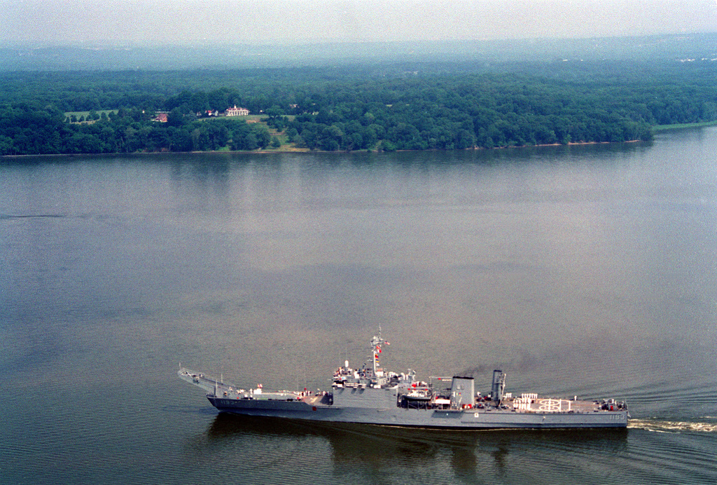 An aerial port side view of the tank landing ship USS FAIRFAX COUNTY (LST-1193) passing opposite Mount Vernon, Virginia, the home of the first President of the United States, George Washington. The ship's crew is presenting a salute to the deceased president