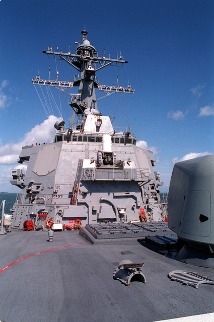 A view from the bow looking aft along the starboard side at the bridge structure of the guided missile destroyer USS ARLEIGH BURKE (DDG-51). On the left side of the bridge is one of the SPY-1D radar fixed antenna arrays. Mounted on the front of the bridge is a 20mm Mark 15 close-in weapon system (CIWS). On the deck forward of the bridge is a Mark 41 vertical launch 32-cell missile launcher