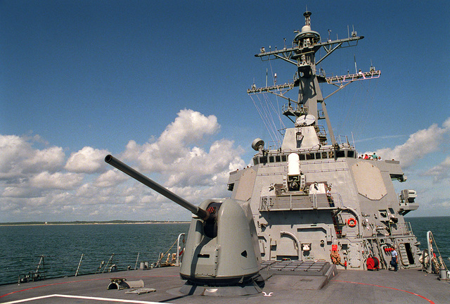 A view from the bow, looking aft, at the port side of the bridge structure of the guided missile destroyer USS ARLEIGH BURKE (DDG-51). In the foreground is the Mark 45 five inch/54 caliber gun mount. Behind the gun mount is the Mark 41 vertical launch 32-cell missile launcher. Mounted on the front of the bridge is a 20mm Mark 15 Close-In Weapon System (CIWS) and to the right side of the bridge in one of the SPY-ID radar fixed antenna arrays