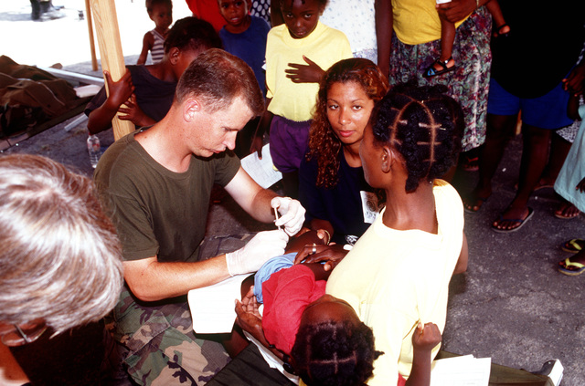 Hospital Corpsman Third Class (HM3) Jeff Mueller, 2nd Medical Force Service Support Group (FSSG) Battalion gives Haitian children their required shots. If they are under 7 years of age they receive a DPT and HIB immunization and they have to be over 9 months old to get an MMR shot. Two tents in Camp 4 were set up for this procedure