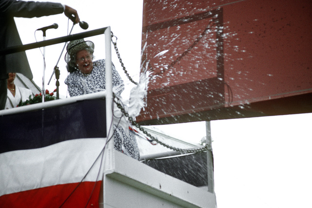 Mrs. Joseph K. Taussig, Jr., ships sponsor, breaks the traditional bottle of champagne over the bow of the guided missile destroyer USS CARNEY (DDG-64) at the conclusion of the christening ceremony and launches the Navy's newest warship