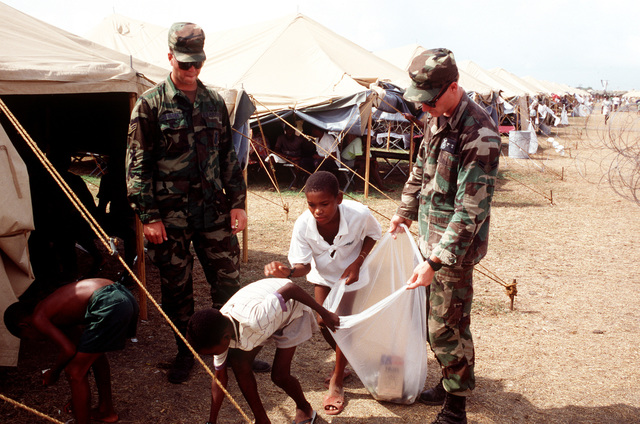 AIRMAN 1ST Class Jeff Leyshon (left) and Samuel Crow (right) from the 2nd Security Police Squadron (SPS), Barksdale, LA, help Haitians with the cleanup of their Camp
