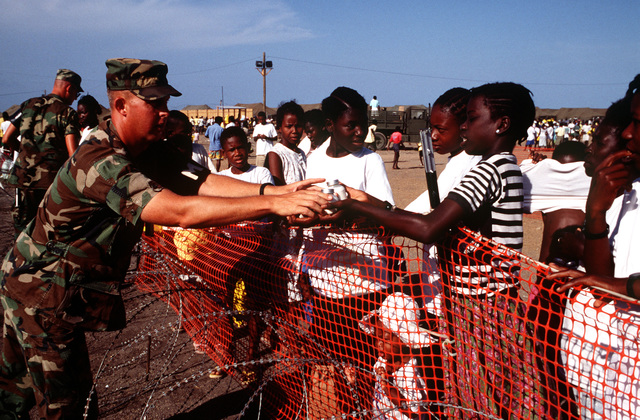SGT. 1ST Class Stephen Holbrook, US Army, 1ST Company, Fort Riley, KS, hands out bottles of formula to Haitian mothers to feed their babies at Camp 3