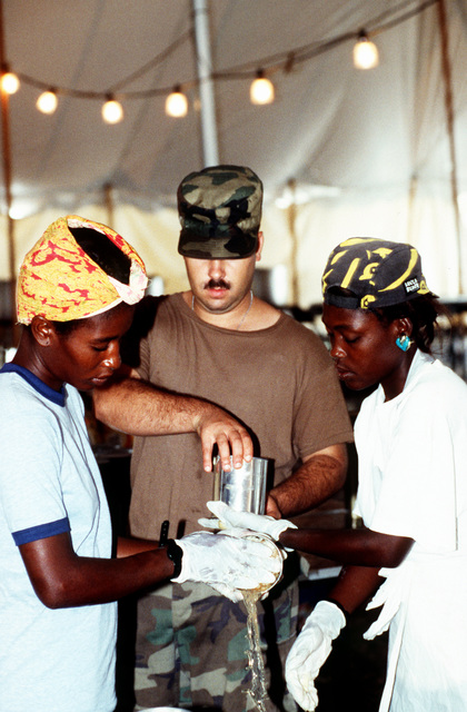 SPC. Phillips, US Army, Hunter Army Airfield, Fort Stewart, GA, helps prepare meals with Haitian refugees that have volunteered to cook in the mess tent at McCallah Field