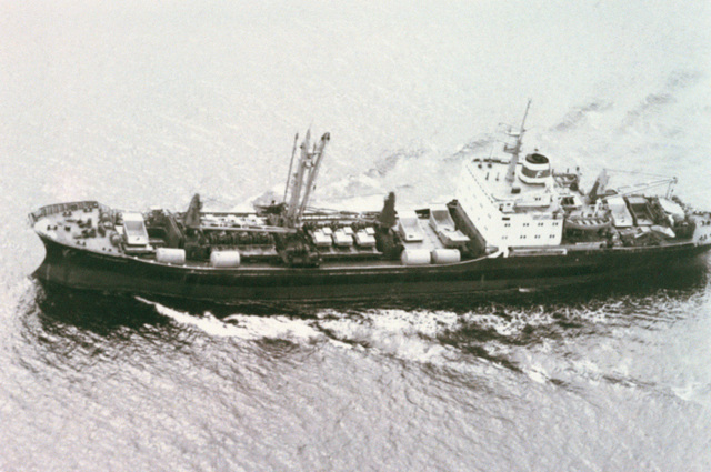 Aerial port side view of the Russian merchant cargo ship STARNIY BOLSHEVIK underway. The ship is carrying various pieces of large construction equipment as deck cargo