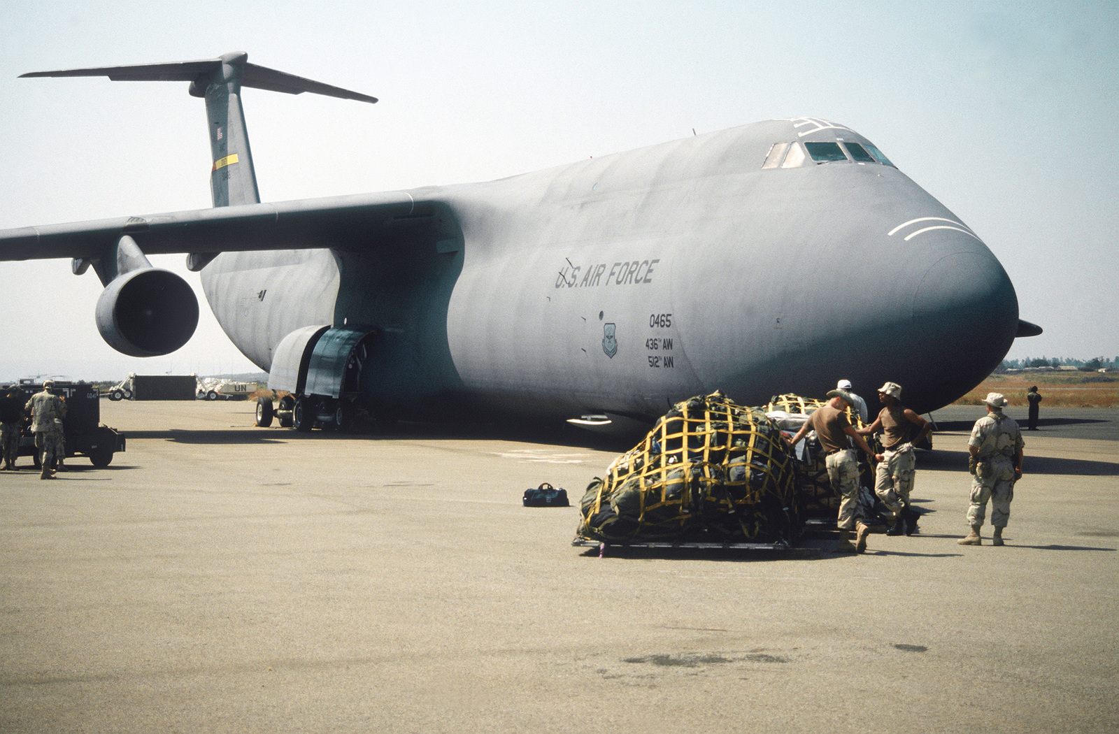 Pallets of Tactical Airlift Control Element (TALCE) equipment on the ramp in front of a 436th Airlift Wing, Dover AFB, Denver, C-5 Galaxy after arriving at Kigali airport