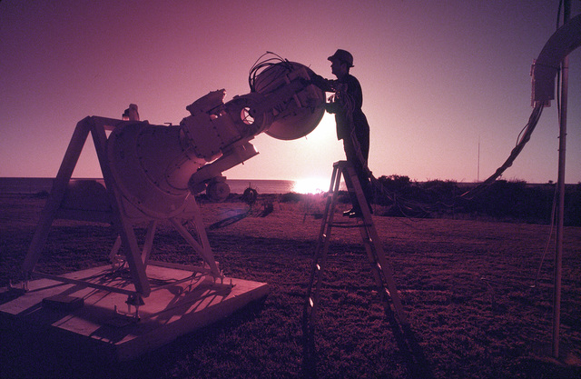 Sunrise silhouettes one of Learmonth's three radio antennas and a maintenance technician. The antenna along with others belong to Detachment 1, 50th Weather Squadron at Learmonth, Australia, which, along with six other Air Weather Service solar observatories around the globe, monitors solar activities 24 hours a day. Exact Date Shot Unknown .Published in AIRMAN Magazine November 1994