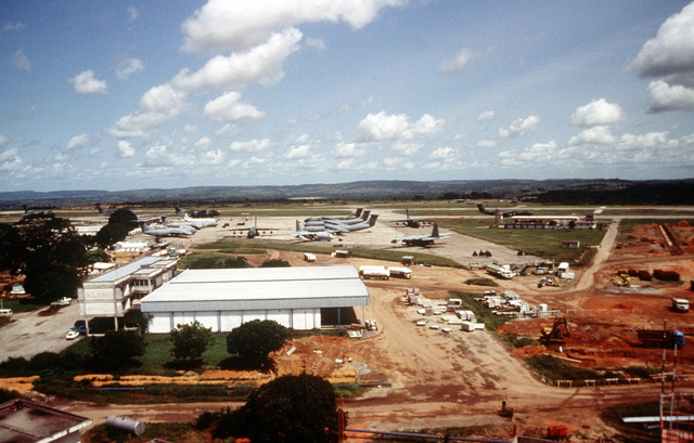 An aerial view of the Moi International Airport. Parked on the ramp in the background are C-5 Galaxys, C-141 Starlifters, and C-130 Hercules aircraft as they take part in the operation