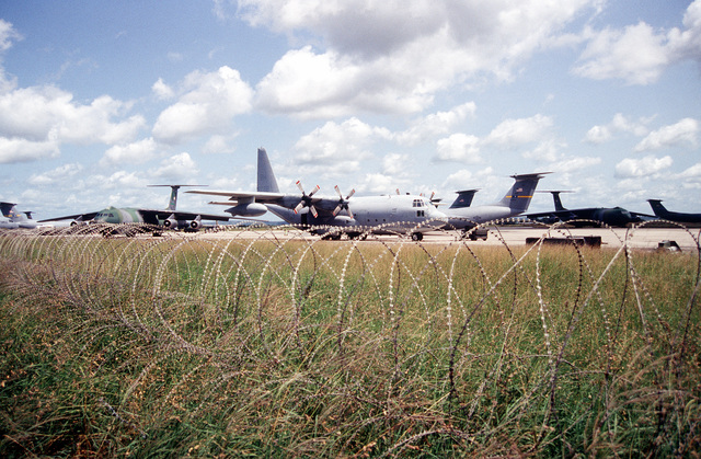 Barbed wire surrounds the flight line ramp at Moi International Airport filled with USAF C-5 Galaxy, C-141 Starlifter, C-130 Hercules and Marine Corp aircraft, all supporting the humanitarian relief effort to Rawanda and Uganda