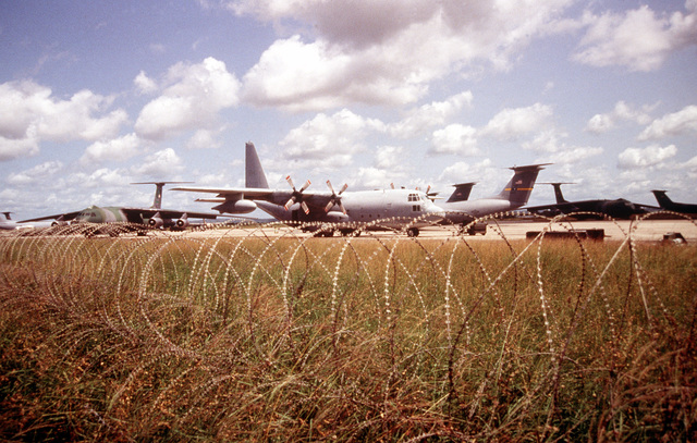 Concertina wire surrounds C-5 Galaxys, C-141 Starlifters, and C-130 Hercules parked on the ramp of the Moi International Airport