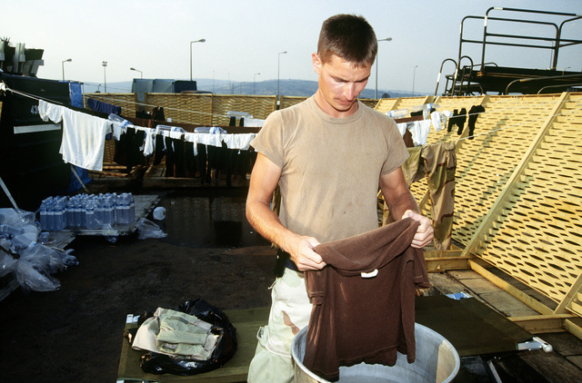 In a makeshift laundry on the flight line ramp, SSGT Richard Jones, 436th Tactical Airlift Control Element (TALCE) Aircraft Generation Squadron (AGS) Dover AFB, Denver washes his clothes. He is part of the United States contingent providing humanitarian relief to Rwanda