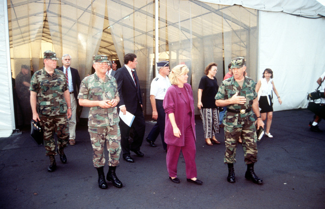 "GEN John Shalikashvili, Chairman of the Joint Chiefs of STAFF, Mrs. Mary ""Tipper"" Gore, wife of Vice President Gore and their parties, leave the temporary warehouse/tent where supplies for the humanitarian relief efforts airlift in Rwanda are stored. (Duplicate image, see also DFST9905478)"