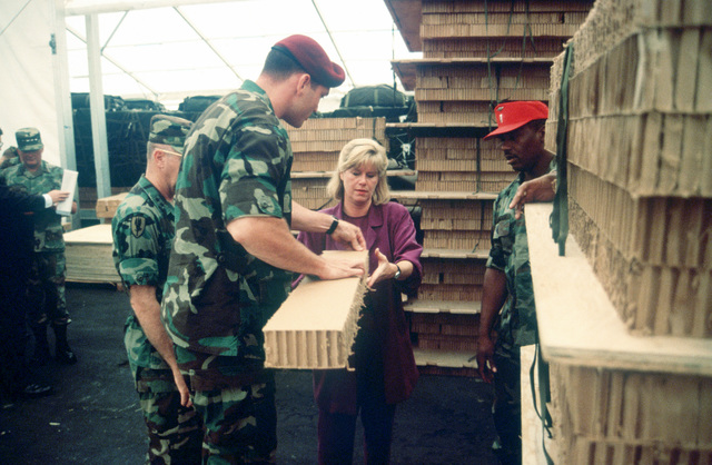 "Mrs. Mary ""Tipper Gore"", wife of Vice President Gore gets a briefing, from airlift specialists, on how the Tri Wall Aerial Delivery Systems (TRIAD) provides protection for the airlift cargo. (Duplicate image, see also DFST9905476)"