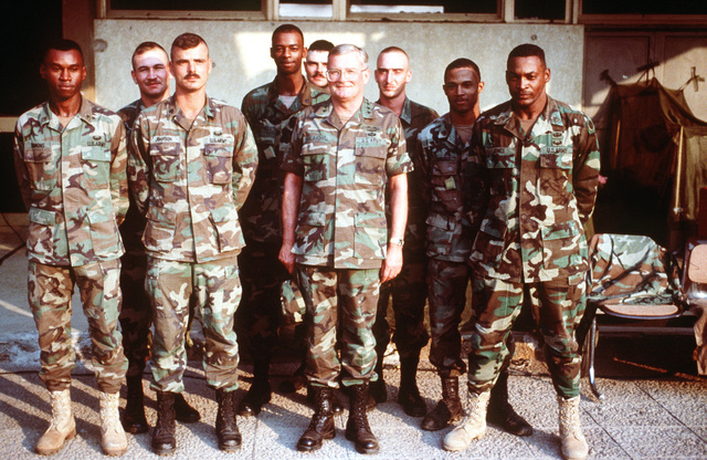 GEN. John M. Shalikashvili, chairman of the Joint Chiefs of STAFF, takes time during his visit to pose for a group picture with the troops. All are dressed in camouflaged fatigues