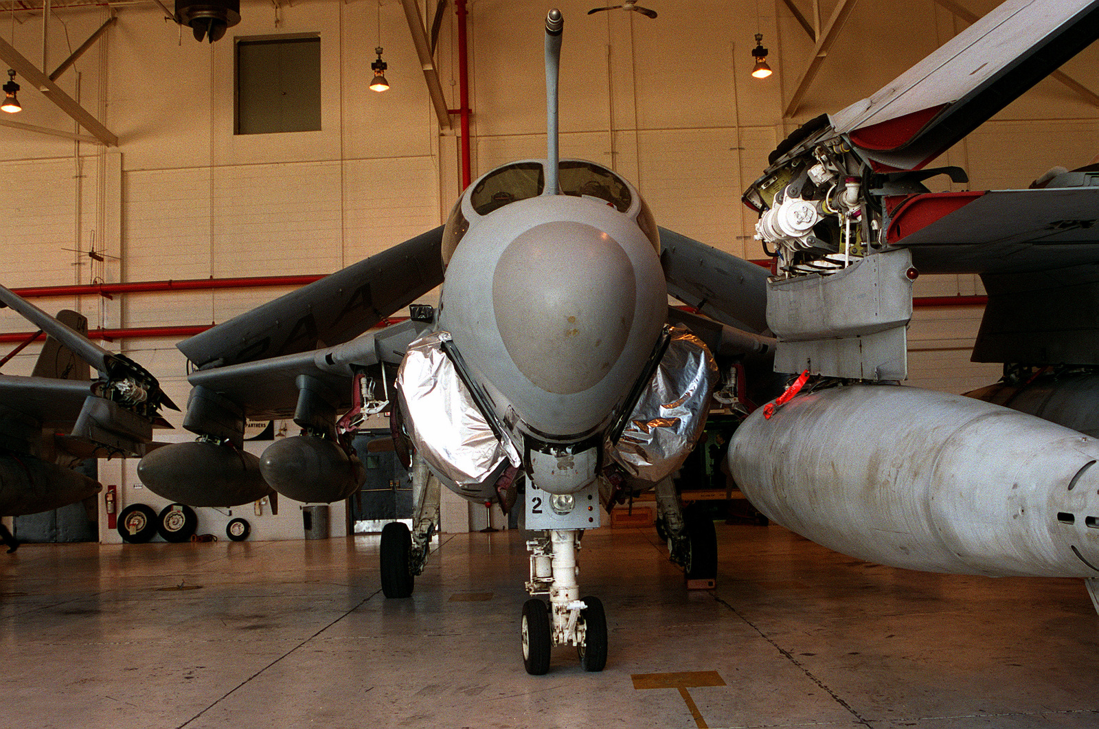 Three A-6E Intruder aircraft of Attack Squadron 35 (VA-35) are shown secured inside hangar III. Their intakes are sealed while the planes are in short term storage (30-day preservation) due to a lack of operating funds