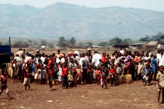 Refugees receive water at one of the many water distribution centers as they make their return journey to Rwanda