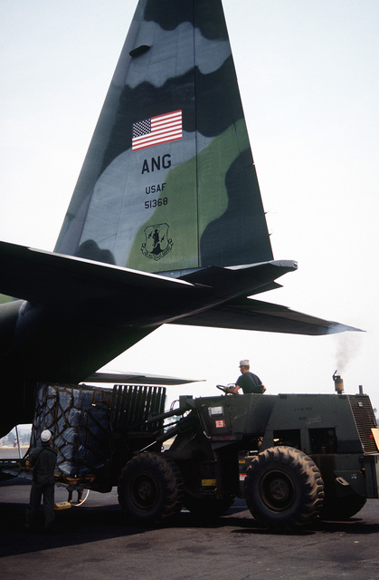 A pallet of relief supplies, mostly biscuits, are downloaded by forklift from a C-130 Hercules assigned to the 136th Airlift Wing, 181st Airlift Squadron, Dallas, Texas ANG at the airport