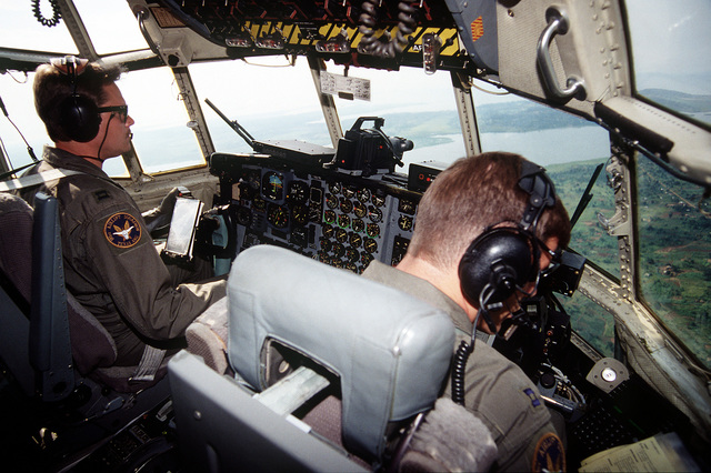 Pilot CPT Rick Ford and co-pilot CPT John Gustafson at their crew positions on the C-130 Hercules assigned to the 136th Airlift Wing, 181st Airlift Squadron, Dallas, Texas ANG in route with relief supplies from Moi International Airport to Entebbe, Uganda