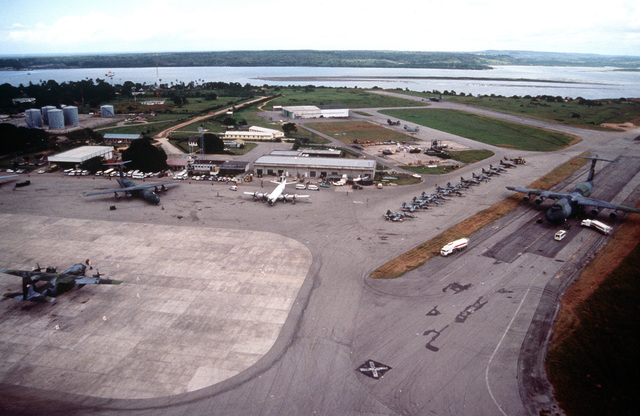 Aerial shot of C-5 Galaxy on the runway, a C-141 and C-130, and other fighter aircraft in background at the airport. Mombasa is one of the main staging areas for airlift missions flying into Goma, Zaire to deliver relief goods to the Rwandan refugees. (Duplicate of DF-ST-99-05500)