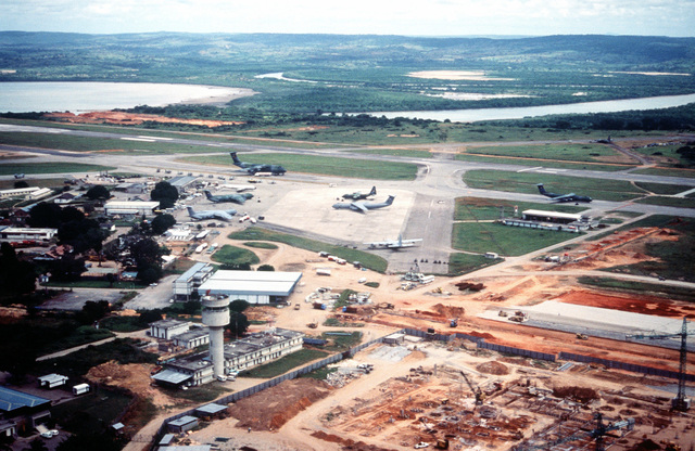 Aerial view of C-141s and a C-130 parked on the ramp and a C-5 on the runway in the background at the airport. In the foreground, construction can be seen. Mombasa is one of the main staging areas for airlift missions flying into Goma, Zaire to deliver relief goods to the Rwandan refugees. (Duplicate image, see also DFST9905501)