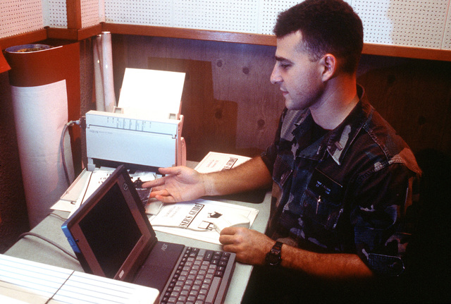 2nd LT. Phil Bellania, 60th Operations Support Squadron (OSS), Travis AFB, CA, Air Mobility Command (AMC) Intelligence augmentee deployed at the air base, uses a laptop computer to work on a handout for aircrews flying humanitarian missions for the operation