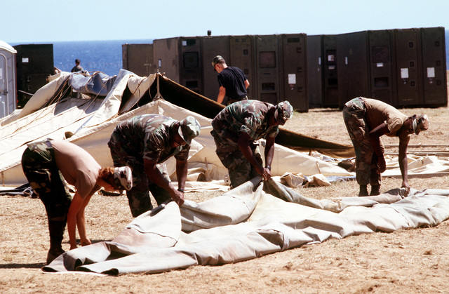 Air Force SGT. Michelle M. Morelli and other Joint Task Force 160 personnel lay out a tent that will be used to house personnel arriving to help handle the flow of Cubans fleeing Cuba