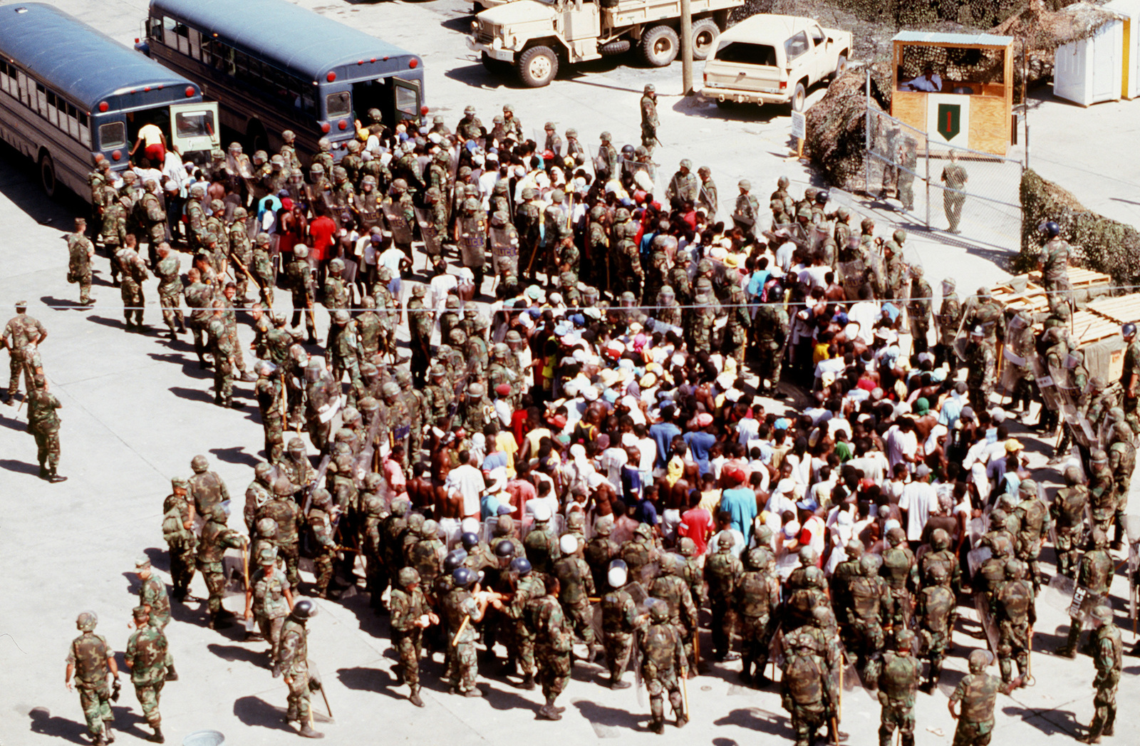Disruptive Haitians are loaded into buses by MPs in riot gear from the 401st and 64th MP Companies. The Haitians jumped the concertina wire and were promptly surrounded by the soldiers. There was no violence and the Haitians were taken to an isolation camp without incident