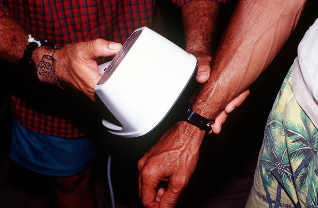 A Cuban man helps in the DMPITS (Deployable Mass Population Identification and Tracking System.) area by scanning bracelets of other Cuban migrants to get them entered in the computer