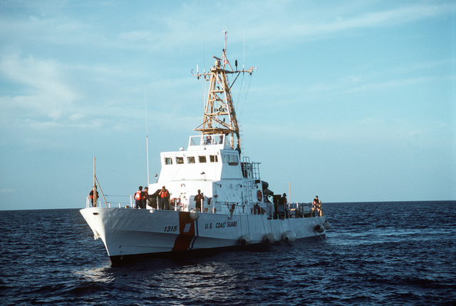 The U.S. Coast Guard cutter MATINICUS (WPB-1315), with a load of Cuban refugees, approaches the dock landing ship USS WHIDBEY ISLAND (LSD-41) for a personnel transfer. The Cuban refugees are being retrieved from small boats, rafts and anything that will float. When the cutters reach maximum capacity, they rendzevous with a U.S. Navy ship and transfer the refugees which are then treansported to the U.S. Naval Base Guantanamo Bay, Cuba