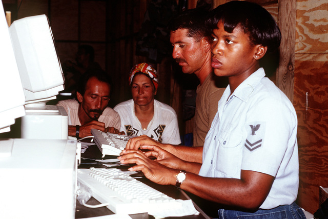 U.S. Navy, DP2 Wanda Smith from the USS EMORY S. LAND and U.S. Air Force STAFF SGT. Octaviano Velasquez from Holloman AFB, New Mexico enter information into the DMPITS (Deployable Mass Population Identification and Tracking System.) computer