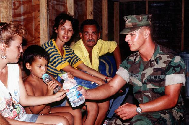 While the new Cuban migrants are waiting to get their DMPITS (Deployable Mass Population Identification and Tracking System.) bracelets, U.S. Marine Lance CPL. Charles Criscione from Fox Company 2/6, Camp Lejeune, NC gives them some bottled water