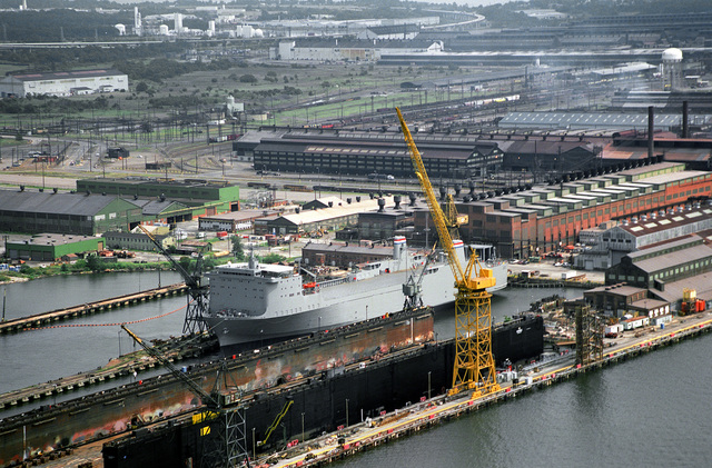 An aerial port bow view of the vehicle transport ship CAPE WRAFT (T-AKR-9964) under conversion and overhaul of the Sparrows Point Extension Yard of the Bethleham Steel Corporation