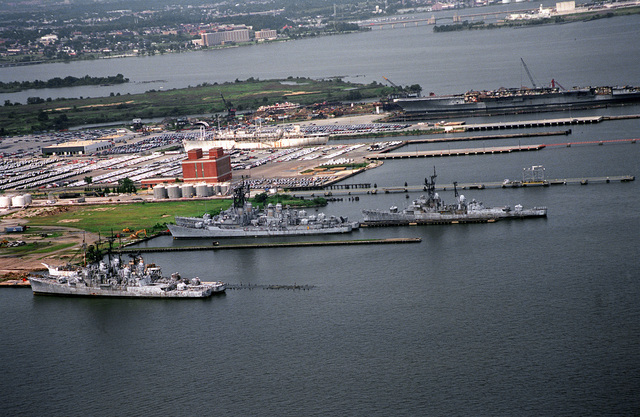 An overall aerial view of the Baltimore Fairfield Terminal area. In the lower section of the photo are four Forest Sherman class destroyers and two Adams class guided missile destroyers waiting to be scrapped at the Baltimore Salvage Company. In the upper portion of the picture is the hulk of the aircraft carrier CORAL SEA (CV-43) being scrapped out at the Seawitch Marine Salvage Company. The white ship at the Maryland Port Authority pier in the center of the photo is the former hospital ship SANCTUARY (AH-17), now owned by Life International