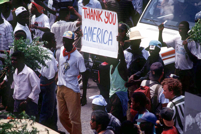 "Outside the Port au Prince Airport, Haitians hold up a ""Thank You America"" sign to show support for American troops who are protecting their city streets and forcing out General Cedras, the self-imposed leader of Haiti, during Operation Uphold Democracy. Exact Date Shot Unknown"