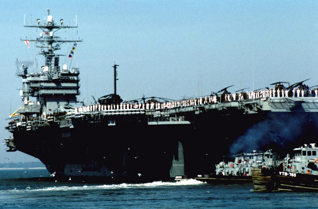 USS DWIGHT D. EISENHOWER (CVN-69) departs from her home port of Norfolk bound for the Caribbean in support of Operation Uphold Democracy. Large harbor tugs assist the nuclear powered aircraft carrier into the channel. Exact Date Shot Unknown
