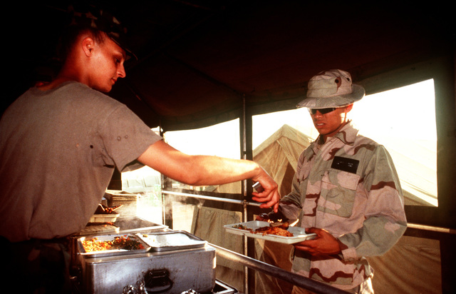 PVT. 2 Brandy Walley from the Headquarters and Headquarters Company (HHC) 7th Battalion, 1ST Brigade, Infantry Division, Katterbach, Germany serve hot meals to U.S. military personnel