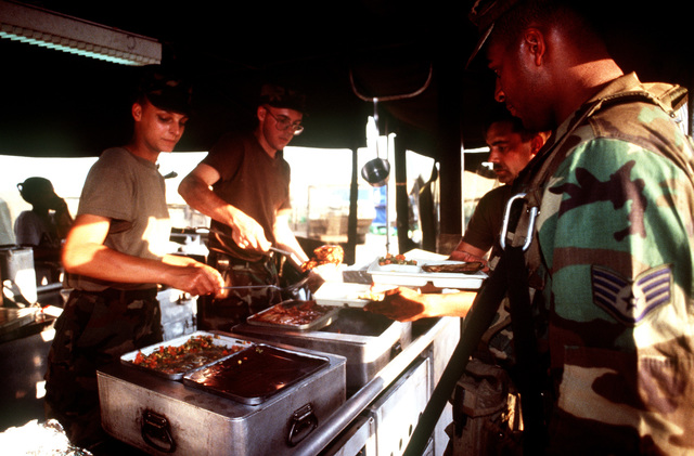 PVT. 2 Brandy Walley from the Headquarters and Headquarters Company (HHC) 7th Battalion, 1ST Brigade, 3rd Infantry Division, Katterbach, Germany serve hot meals to US military personnel