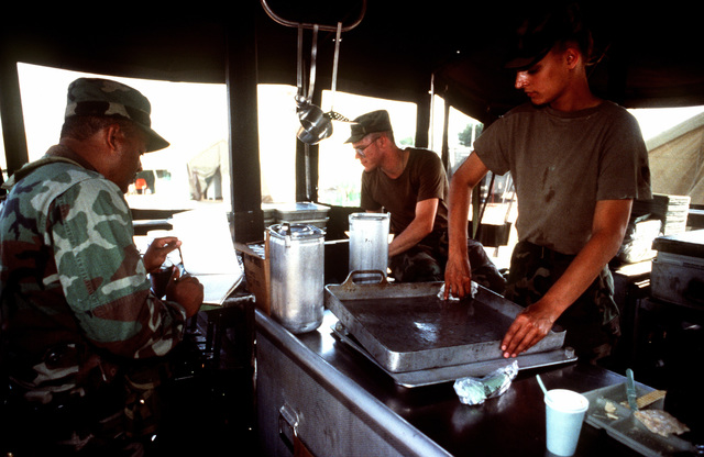 SGT. 1ST Class Tomas Delgadillo, PVT. 2 Brandy Walley and PFC Shawn Gibbs from the Headquarters and Headquarters Company (HHC) 7th Battalion 1ST Brigade, 3rd Infantry Division, Katterbach, Germany prepare to serve meals to US military personnel deployed at the airport